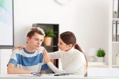 Psicólogo de sexo femenino joven que trabaja con el muchacho del adolescente en oficina Fotos de archivo