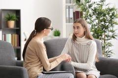 Psicólogo de sexo femenino joven que trabaja con la muchacha del adolescente en oficina Imagen de archivo