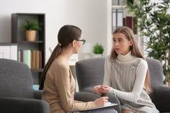 Psicólogo de sexo femenino joven que trabaja con la muchacha del adolescente en oficina Imágenes de archivo libres de regalías