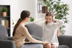 Psicólogo de sexo femenino joven que trabaja con la muchacha del adolescente en oficina Foto de archivo libre de regalías