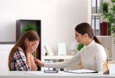 Psicólogo de sexo femenino joven que trabaja con la muchacha del adolescente en oficina Fotografía de archivo