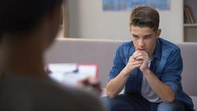 Psicólogo de visita do adolescente ansioso para a sessão de terapia pessoal, problemas video estoque