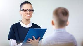 Psicólogo del niño de la mujer o doctor bonito del terapeuta de discurso que habla con el paciente del niño que toma notas metrajes