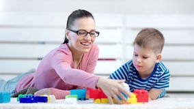 Psicólogo e bebê de sorriso da criança da mulher que jogam com o bloco colorido do construtor que encontra-se no assoalho video estoque