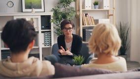 Psicólogo experiente que dá o conselho à mãe e ao adolescente da família no escritório video estoque