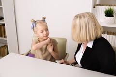 Psic?logo f?mea com o assento do paciente da crian?a interno na mesa e a fala Conceito do problema da crian?a fotografia de stock