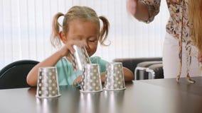 Psicólogo que testa a menina da criança pequena durante o jogo de shell com copos filme