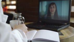 Psicólogo que toma notas mientras que en línea consulta metrajes