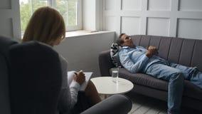Psicólogo que visita descontentado triste del hombre almacen de video