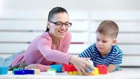 Psicólogo y bebé sonrientes del niño de la mujer que juegan con el bloque colorido del constructor que miente en piso almacen de video