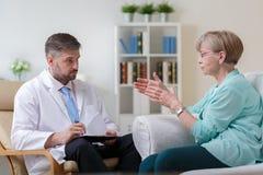 Psichiatra che ascolta il suo paziente femminile immagini stock libere da diritti