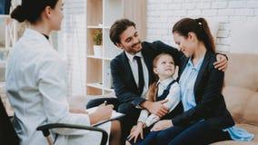 Psicologo felice di consultazione del bambino di sguardo dei genitori fotografie stock libere da diritti