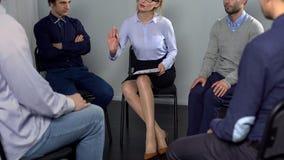 Psicologo femminile che calma uomo aggressivo alla terapia del gruppo, dipendenza fotografia stock libera da diritti
