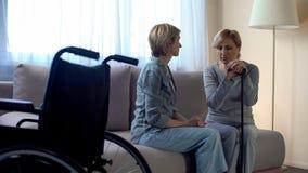 Psicologo femminile che sostiene donna senior disabile sola alla casa di cura immagine stock libera da diritti