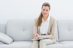 Psicologo femminile sorridente che si siede sul sofà Fotografia Stock