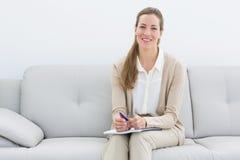 Psicologo femminile sorridente che si siede sul sofà Immagine Stock