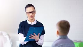 Psicologo infantile sicuro della donna professionale che fa prova con il ragazzo alla sessione di psicoterapia video d archivio