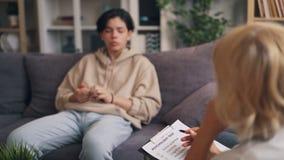 Psicoterapeuta de sexo femenino que trabaja con el adolescente que hace las preguntas que llevan a cabo la carta metrajes