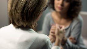 Psicoterapeuta di signora che conforta e che tiene la mano femminile del tossicomane, terapia fotografie stock libere da diritti