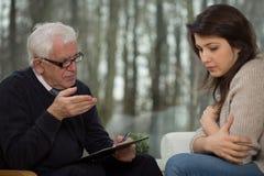 Psicoterapeuta mayor y paciente joven Fotografía de archivo