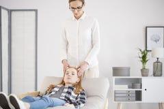 Psicoterapeuta que da masajes a la cabeza Imagenes de archivo