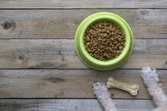 Psiego jedzenia i psa łapa na drewno stole Fotografia Royalty Free