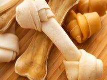 Psiego jedzenia kość na ciapania drewnie na bielu zdjęcia royalty free