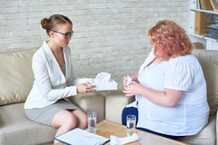 Psiquiatra de sexo femenino de apoyo Consulting Obese Woman imagenes de archivo