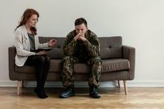 Psiquiatra que habla con su paciente enojado mientras que se sienta en un sofá fotos de archivo