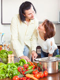 Psitive housewife with husbant cooking with fresh vegetables at Royalty Free Stock Photography