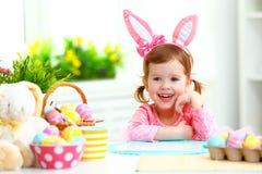 Påsk den lyckliga barnflickan med kaninen gå i ax med kulöra ägg och f Arkivbilder