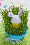 Påskgarnering med det gulliga ägget i kaninhatt Arkivfoton