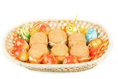 Påskägg och hemlagade söta tårtor i korg Royaltyfri Foto