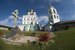 In the Pskov Kremlin. Veche area near the walls of Trinity Cathedral in Pskov Kremlin and the memorial cross to the 1100th anniversary of Pskov Royalty Free Stock Photos