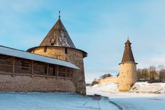 Pskov Kremlin towers separated by the frozen river mouth Pskova. Voskresenskaya and Ploskaya towers, located on both banks of the river Pskova in the confluence Royalty Free Stock Image