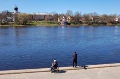 Pskov, Russia 04 può 2017 Un uomo in una pesca della sedia a rotelle Numerosi pescatori sul fiume di Velikaya vicino al Cremlino fotografia stock