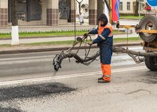 Road Worker is putting hot asphalt to repair pits on the road in the center of Pskov, Russia. Pskov, Russian Federation - May 5, 2018: Road Worker is putting hot Royalty Free Stock Images