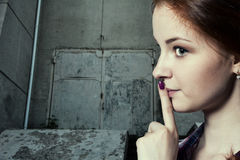 Psst - a beautiful girl with pigtails making a shushing gesture Royalty Free Stock Photography