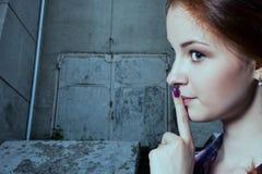 Psst - een mooi meisje die met vlechten een doen zwijgend gebaar maken stock afbeeldingen
