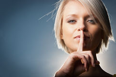 Psst - en härlig kvinna som gör en hyssja ner gest Arkivbild