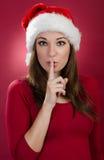 Psst - kvinna med den santa hatten arkivfoton