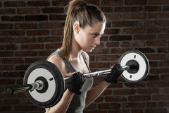 PSweat beautiful girl lifting dumbbells on dark background. Portrait of Sweat beautiful girl lifting dumbbells on dark background Stock Images