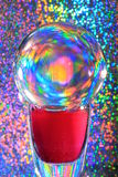 Psychedelic. A glass orb is placed on a vase filled with reddish liquid. Refracting the light from the multi-reflecting foil behind it, it takes on a psychedelic Royalty Free Stock Photography