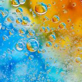Psychedelic oil drops. Oil drops on a water surface with colour background stock image