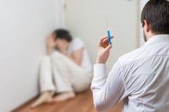 Psychiatersdoktor hält Spritze Verrückter oder geisteskranker Patient im Hintergrund Stockfotografie