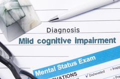 Psychiatric Diagnosis Mild Cognitive Impairment. Medical book or form with the name of diagnosis Mild Cognitive Impairment is on t. Able of doctor surrounded by royalty free stock photography