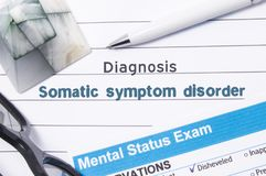 Psychiatric Diagnosis Somatic Symptom Disorder. Medical book or form with the name of diagnosis Somatic Symptom Disorder is on tab. Le of doctor surrounded by stock photo