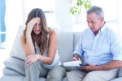 Psychiatrist advising depressed pregenat woman. Psychiatrist advising to depressed pregnant women while sitting on sofa Royalty Free Stock Images
