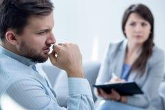 Psychiatrist diagnosing patient. Photo of female psychiatrist diagnosing her male patient Stock Photo