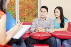 Psychiatrist giving motivation for young couple. Portrait of husband and wife sitting in the red sofa while psychiatrist giving motivation, with autumn Royalty Free Stock Photo
